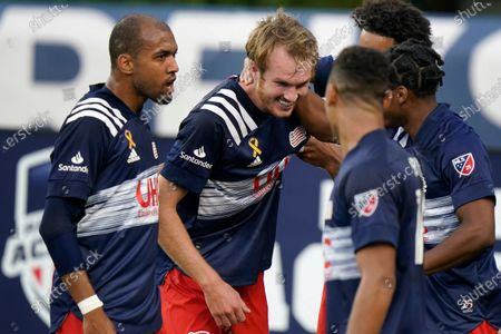 New England Revolution's Henry Kessler, center, celebrates with teammates Teal Bunbury, left, and Brandon Bye, front right, after scoring in the first half of an MLS soccer match against the Montreal Impact, in Foxborough, Mass