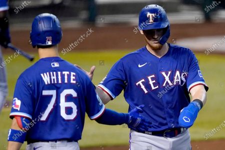 Texas Rangers' Sam Huff greets Eli White (76) after scoring on a base hit by teammate Anderson Tejeda during the fourth inning of a baseball game against the Arizona Diamondbacks, in Phoenix