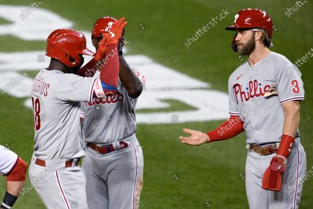 Philadelphia Phillies' Didi Gregorius, left, celebrates his three-run home run with Andrew McCutchen, center, and Bryce Harper during the ninth inning of the team's baseball game against the Washington Nationals, in Washington