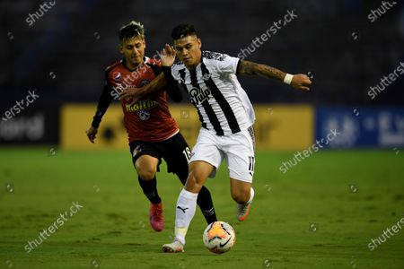 Caracas' Anderson Contreras (L) in action against Adrian Martinez of Libertad during a Copa Libertadores group H soccer match between Caracas FC of Venezuela and Libertad of Paraguay, at the Olympic stadium in Caracas, Venezuela, 23 September 2020.
