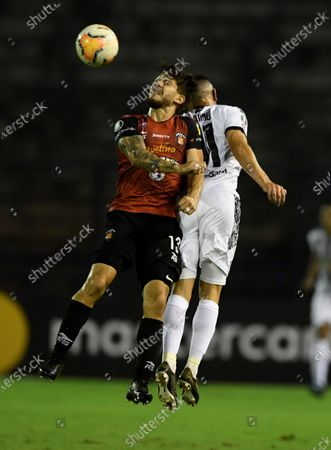 Caracas' Carlos Rivero (L) in action against Adrian Martinez of Libertad during a Copa Libertadores group H soccer match between Caracas FC of Venezuela and Libertad of Paraguay, at the Olympic stadium in Caracas, Venezuela, 23 September 2020.
