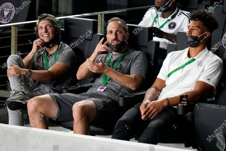 Newly signed Inter Miami forward Gonzalo Higuain, center, sits with midfielder George Acosta, left, and goalkeeper Drake Callender, right, before an MLS soccer match against the New York Red Bulls, in Fort Lauderdale, Fla
