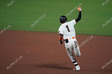 San Francisco Giants' Mauricio Dubon raises his arm as he runs the bases after hitting a three-run home run against the Colorado Rockies during the fifth inning of a baseball game, in San Francisco