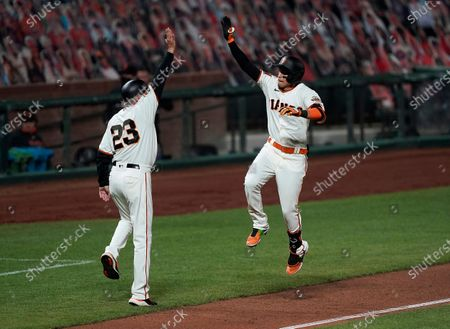 San Francisco Giants' Mauricio Dubon gives a virtual high-five to third base coach Ron Wotus (23) after hitting a three-run home run against the Colorado Rockies during the fifth inning of a baseball game, in San Francisco