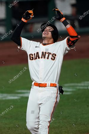 San Francisco Giants' Mauricio Dubon points to the sky as he crosses home plate after hitting a three-run home run against the Colorado Rockies during the fifth inning of a baseball game, in San Francisco