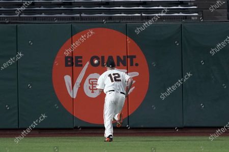 San Francisco Giants left fielder Alex Dickerson chases down a double by Colorado Rockies' Raimel Tapia during the fifth inning of a baseball game, in San Francisco