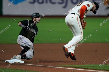 Colorado Rockies' Garrett Hampson slides safely into third base past San Francisco Giants third baseman Evan Longoria during the seventh inning of a baseball game, in San Francisco