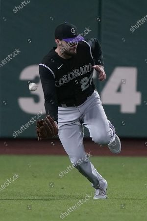 Colorado Rockies left fielder Sam Hilliard can't make the catch on a hit by San Francisco Giants' Steven Duggar during the eighth inning of a baseball game, in San Francisco. San Francisco won 7-2