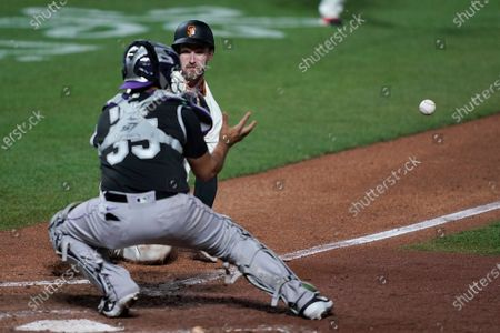 San Francisco Giants' Steven Duggar, rear, is tagged out at home by Colorado Rockies catcher Elias Diaz (35) during the eighth inning of a baseball game, in San Francisco. The Giants won 7-2