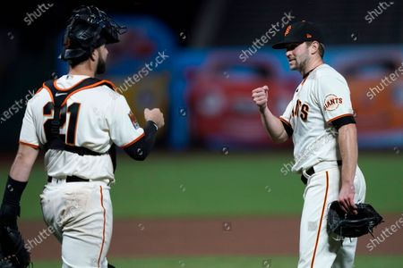 San Francisco Giants relief pitcher Sam Selman, right, is congratulated by catcher Joey Bart after the Giants' 7-2 victory over the Colorado Rockies in a baseball game, in San Francisco