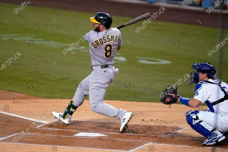 Oakland Athletics' Robbie Grossman follows through on an RBI double during the first inning of the team's baseball game against the Los Angeles Dodgers, in Los Angeles