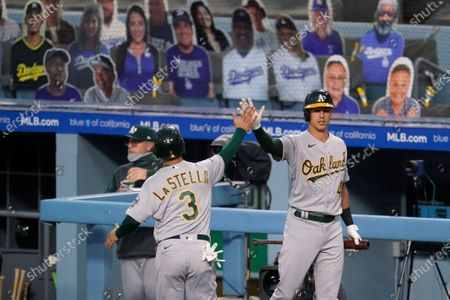 Oakland Athletics' Tommy La Stella (3) is high-fived by Jake Lamb after La Stella scored on a double by Robbie Grossman during the first inning of the team's baseball game against the Los Angeles Dodgers, in Los Angeles