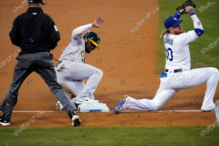 Oakland Athletics' Marcus Semien, center, slides safely into third base after a throwing error to Los Angeles Dodgers third baseman Justin Turner, right, from center fielder Cody Bellinger on fly ball from Mark Canha during the first inning of a baseball game, in Los Angeles. Semien went on to score on the error