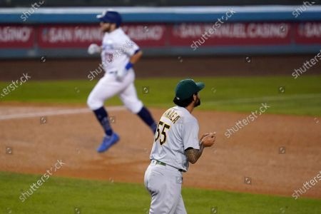 Stock Image of Oakland Athletics starting pitcher Sean Manaea rubs up a new ball after giving up a two-run home run to Los Angeles Dodgers' Max Muncy, rear, during the third inning of a baseball game, in Los Angeles