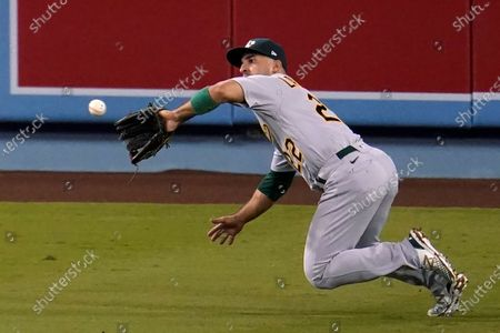 Oakland Athletics center fielder Ramon Laureano makes a diving catch on a line drive from Los Angeles Dodgers' Mookie Betts during the seventh inning of a baseball game, in Los Angeles
