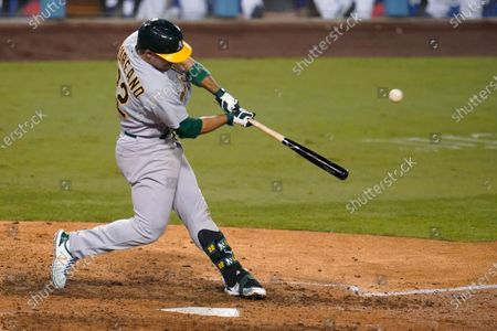 Oakland Athletics' Ramon Laureano swings for a two-run home run during the ninth inning of the team's baseball game against the Los Angeles Dodgers, in Los Angeles