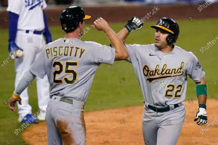 Oakland Athletics' Ramon Laureano, right, celebrates his two-run home run with Stephen Piscotty (25) during the ninth inning of the team's baseball game against the Los Angeles Dodgers, in Los Angeles