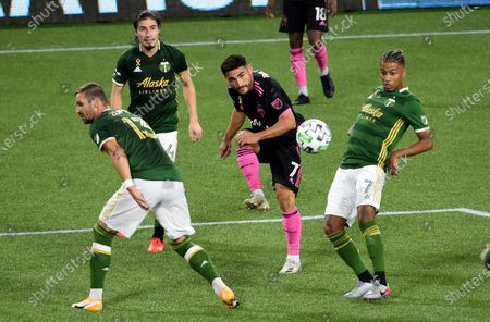 Seattle Sounders midfielder Cristian Roldan, center, puts a shot on goal as Portland Timbers defender Dario Zuparic, left, and forward Andy Polo, right, defend during the second half of an MLS soccer match in Portland, Ore