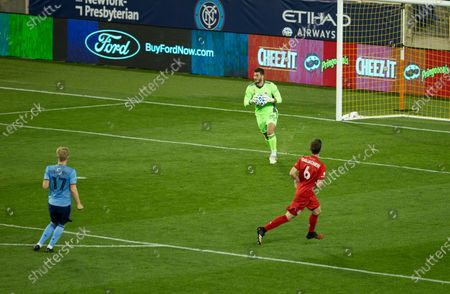 Stock Photo of Goalkeeper Alex Bono (25) of Toronto FC saves during MLS regular season game against NYCFC at Red Bull Arena. Game was played without fans because of COVID-19 pandemic precaution. Toronto FC won 1 - 0. All supporting staff and players on the bench were wearing facial masks and kept social distances.