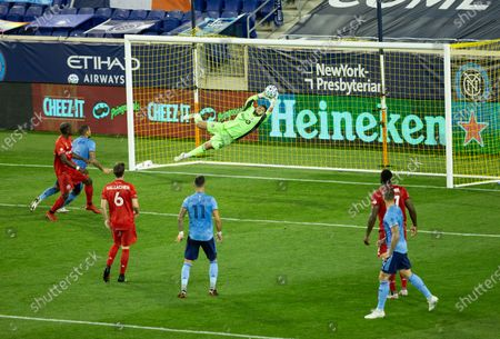 Goalkeeper Alex Bono (25) of Toronto FC saves during MLS regular season game against NYCFC at Red Bull Arena. Game was played without fans because of COVID-19 pandemic precaution. Toronto FC won 1 - 0. All supporting staff and players on the bench were wearing facial masks and kept social distances.