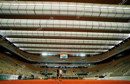 Rafael Nadal of Spain practices under the roof on Philippe Chatrier Court watched by coach Carlos Moya