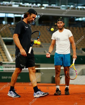 Rafael Nadal of Spain chats with coach Carlos Moya as he practices under the roof on Philippe Chatrier Court