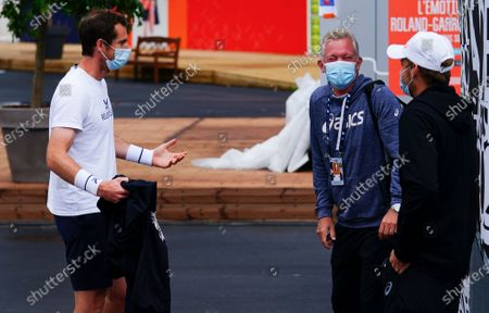 Stock Picture of An animated Andy Murray jokes with Thomas Johansson, David Goffin's coach, as he waits outside his practice court in between rain showers
