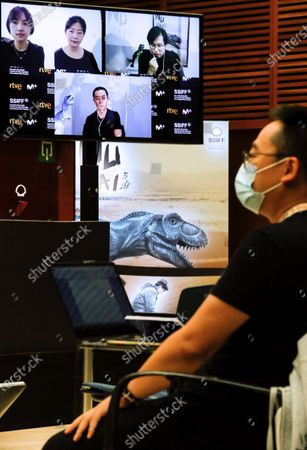 A journalist interviews, via video-conference, Chinese film director Ziang Zhou (R, up), actor Huang Xuan (down) and producers Luna Wang and Yini Qian during an online presentation of their movie 'Wuhai' at the 68th annual San Sebastian International Film Festival (SSIFF), in San Sebastian, Spain, 24 September 2020. The film festival runs from 18 to 26 September 2020 under safety measures like obligatory face mask use and red carpets without public due to the Covid-19 coronavirus pandemic. Organizers have also reduced the number of film screenings as well as the seating capacity in cinemas.