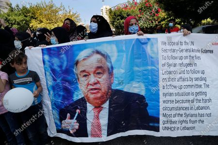 Syrian refugees hold a banner that shows a portrait of the U.N. Secretary General Antonio Guterres, as they protest outside the headquarters of the United Nations refugee agency, UNHCR, demanding to be moved out of Lebanon which is undergoing its worse economic crisis in history with rising unemployment and poverty levels, in Beirut, Lebanon, . Lebanon, home to nearly 1 million Syrian refugees, has called for international help to secure their safe return, saying that they can no longer afford to host them