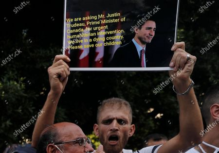 Syrian refugee holds up a sign with a portrait of Canada's Prime Minister Justin Trudeau, during a protest outside the headquarters of the United Nations refugee agency, UNHCR, demanding to be moved out of Lebanon, which is undergoing its worse economic crisis in history with rising unemployment and poverty levels, in Beirut, Lebanon, . Lebanon, home to nearly 1 million Syrian refugees, has called for international help to secure their safe return, saying that they can no longer afford to host them