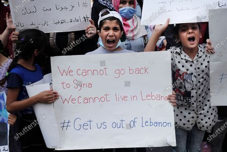 Syrian refugees shout slogans as they protest outside the headquarters of the United Nations refugee agency, UNHCR, demanding to be moved out of Lebanon which is undergoing its worse economic crisis in history with rising unemployment and poverty levels, in Beirut, Lebanon, . Lebanon, home to nearly 1 million Syrian refugees, has called for international help to secure their safe return, saying that they can no longer afford to host them