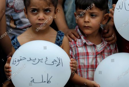 """Syrian refugee holds a balloon with Arabic that reads: """"refugee needs all their rights,"""" during a protest outside the headquarters of the United Nations refugee agency, UNHCR, demanding to be moved out of Lebanon, which is undergoing its worse economic crisis in history with rising unemployment and poverty levels, in Beirut, Lebanon, . Lebanon, home to nearly 1 million Syrian refugees, has called for international help to secure their safe return, saying that they can no longer afford to host them"""