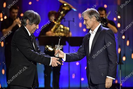 Stock Picture of Actor and film director Viggo Mortensen, right, salutes after receiving the Donostia Award from Agustin Diaz Yanes for his contribution to the cinema during the 68th San Sebastian Film Festival, in San Sebastian, northern Spain