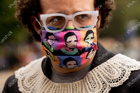 Ryan Cooper of St. Louis wears a jabot and mask depicting the image of late US Supreme Court Justice Ruth Bader Ginsburg as he stands across the street from the Supreme Court as people pay their respects to Ginsburg, in Washington, DC, USA, 24 September 2020.