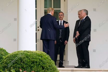President Donald Trump, left, speaks with White House counsel Pat Cipollone, left, national security adviser Robert O'Brien and White House chief of staff Mark Meadows outside the Oval Office of the White House after visiting the Supreme Court to pay respects to Justice Ruth Bader Ginsburg, in Washington