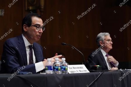 Federal Reserve Chair Jerome Powell, right, listens as Treasury Secretary Steve Mnuchin testifies during the Senate's Committee on Banking, Housing, and Urban Affairs hearing examining the quarterly CARES Act report to Congress on Capitol Hill, in Washington