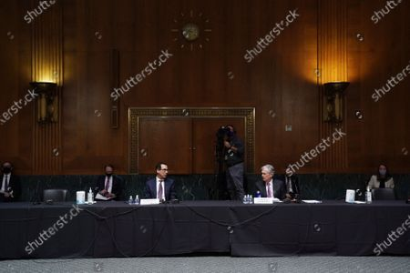 Federal Reserve Chair Jerome Powell, right, and Treasury Secretary Steve Mnuchin await to testify during the Senate's Committee on Banking, Housing, and Urban Affairs hearing examining the quarterly CARES Act report to Congress on Capitol Hill, in Washington