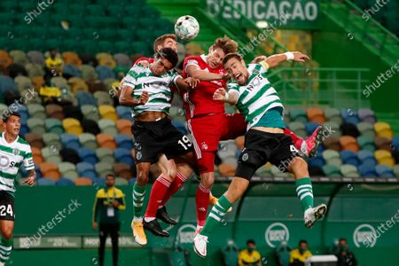 Stock Image of Aberdeen's Marley Watkins, center, jumps for the ball with Sporting's Tiago Tomas, left, and Sebastian Coates, right, during the Europa League third qualifying round soccer match between Sporting CP and Aberdeen at the Alvalade stadium in Lisbon