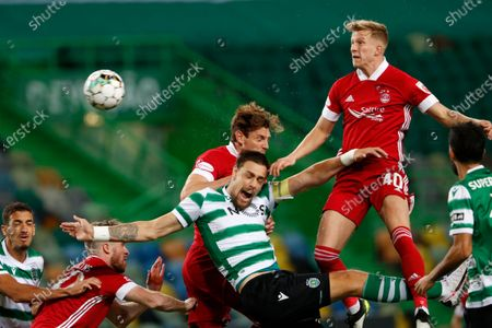 Stock Picture of Sporting's Sebastian Coates, center, jumps for the ball with Aberdeen's Ashton Taylor, background and Ross McCrorie, right, during the Europa League third qualifying round soccer match between Sporting CP and Aberdeen at the Alvalade stadium in Lisbon