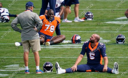 Denver Broncos head coach Vic Fangio, left, confers with newly-signed quarterback Blake Bortles as he stretches at NFL football practice, in Englewood, Colo