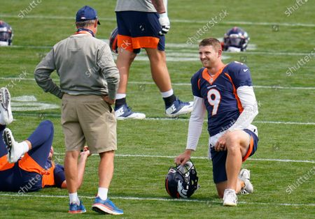 Denver Broncos head coach Vic Fangio, left, jokes with quarterback Jeff Driskel before drills during an NFL football practice, in Englewood, Colo