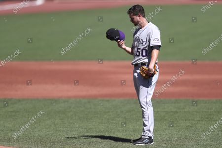 Colorado Rockies' Chi Chi González looks at his hat after allowing two runs in the first inning against the San Francisco Giants during the second inning of a baseball game in San Francisco