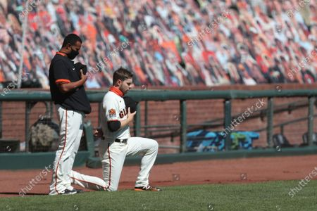 San Francisco Giants' Austin Slater, right, kneels next to teammate Wandy Peralta during the national anthem before a baseball game against the Colorado Rockies in San Francisco