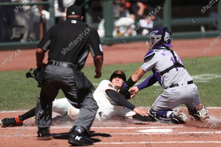 San Francisco Giants' Wilmer Flores is tagged out at home by Colorado Rockies' Tony Wolters during the second inning of a baseball game in San Francisco