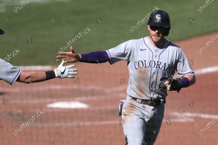 Colorado Rockies' Trevor Story is congratulated after scoring against the San Francisco Giants on a Josh Fuentes single during the seventh inning of a baseball game in San Francisco