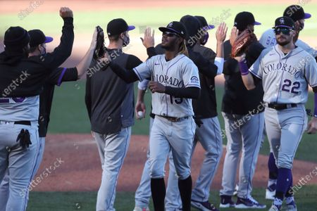 Colorado Rockies' Raimel Tapia, center, and teammates celebrate after defeating the San Francisco Giants 5-4 in 11 innings during a baseball game in San Francisco