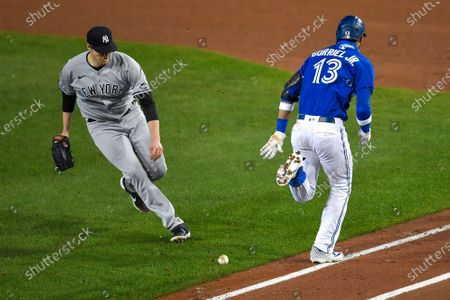 New York Yankees pitcher Jordan Montgomery, left, moves in to field a grounder by Toronto Blue Jays' Lourdes Gurriel Jr., who was safe at first during the fourth inning of a baseball game in Buffalo, N.Y