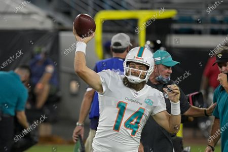 Miami Dolphins quarterback Ryan Fitzpatrick warms up before an NFL football game against the Jacksonville Jaguars, in Jacksonville, Fla