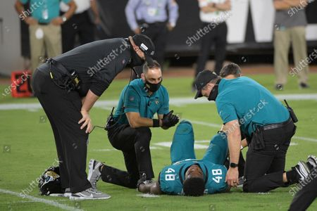 Team personnel check on Jacksonville Jaguars outside linebacker Leon Jacobs (48) after he was injured during the first half of an NFL football game against the Miami Dolphins, in Jacksonville, Fla