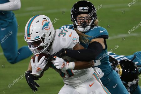 Miami Dolphins running back Myles Gaskin (37) tries to escape a tackle by Jacksonville Jaguars free safety Andrew Wingard, right, during the first half of an NFL football game, in Jacksonville, Fla